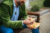 Fotografie Teilansicht der Mann im grünen Samtjacke mit Pommes frites sitzend auf Bank auf Straße