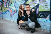 Fotografie couple in fashionable outfit with french fries sitting near wall with graffiti on street