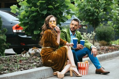 fashionable couple in velvet clothing with fried chicken legs and drinks on street