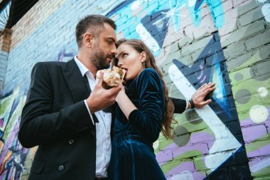 low angle view of couple in luxury clothing with hot dogs standing near graffiti on wall on street