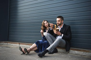 couple in fashionable clothing with asian takeaway food sitting on street