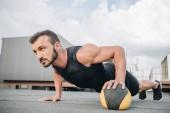 pohledný sportovec dělá push up s medicinbal na střeše