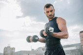 handsome sportsman training with dumbbells on roof and looking at biceps