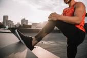 Fotografia immagine potata di sportivi che allunga i piedini sul tetto durante il tramonto