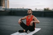 handsome sportsman stretching legs on yoga mat on roof