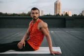 pohledný muž, spočívající na jógu po praktikování jógy na střeše