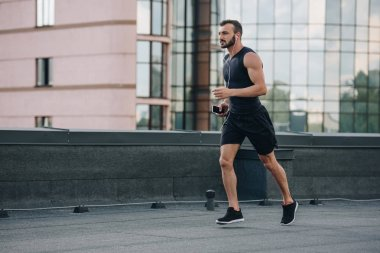 side view of handsome sportsman running and listening music with smartphone on roof
