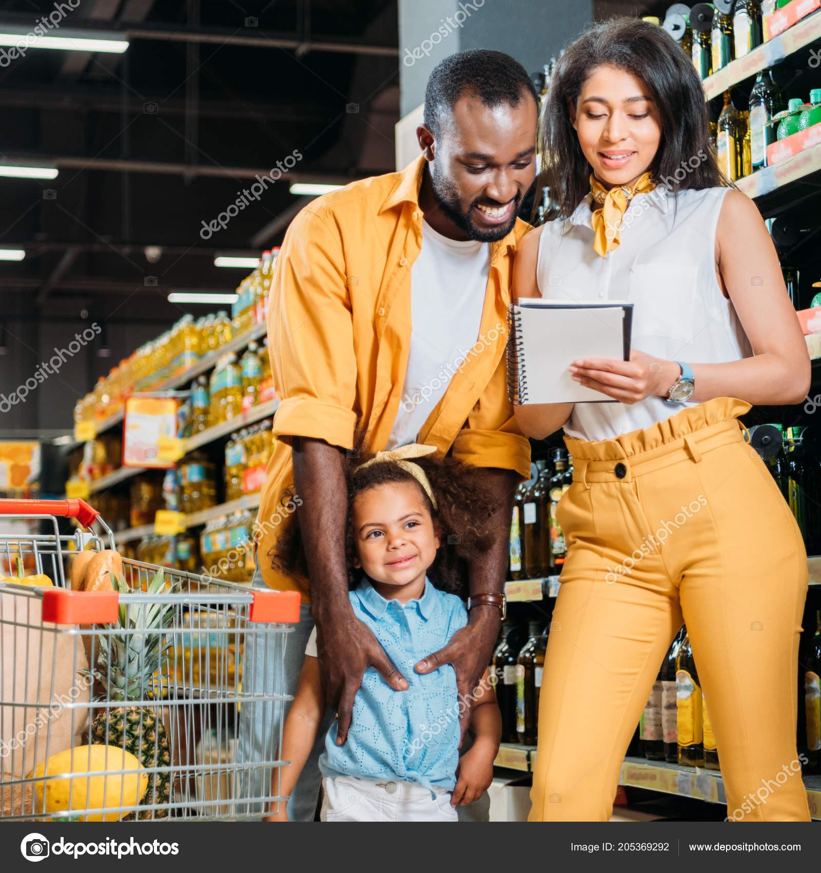 feliz familia afroamericana con hija mirando lista supermercado