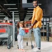 Fotografia sorridente uomo afroamericano che sta con la figlia vicino carrello di acquisto in supermercato