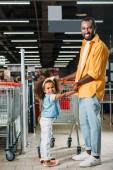 americký muž, který držel ruce dcery poblíž nákupní vozík v supermarketu