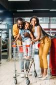 Fotografia giovani coppie felici dellafroamericana con la piccola figlia in piedi nel carrello di acquisto in ipermercato