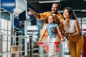 Fotografia uomo afroamericano che punta di dito alla piccola figlia e moglie in supermercato sorridente
