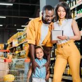 Fényképek boldog afrikai-amerikai család lányát keresi a bevásárló listát a szupermarketben