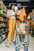 Fényképek african american woman with shopping list pointing by finger to boyfriend with shopping trolley in supermarket