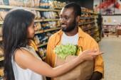 mladá africká americká žena ukazující na přítele s papírový sáček s jídlem v supermarketu