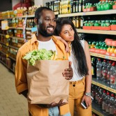 Fényképek smiling african american couple with paper bag and smartphone in grocery store