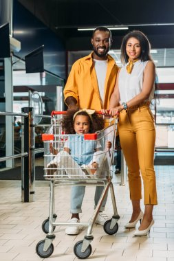 adorable african american kid sitting in shopping trolley while her parents standing near in supermarket