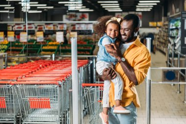 happy african american man embracing and holding little daughter in grocery store