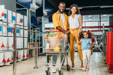happy african american couple and their daughter standing near shopping trolley with food in supermarket
