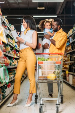 Smiling african american man holding daughter while his wife choosing food with shopping list in supermarket stock vector