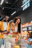 sorridente donna afro-americana ne su smartphone mentre suo marito e sua figlia in piedi vicino a con carrello di acquisto in supermercato