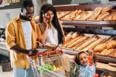 donna afro-americana ne su smartphone mentre suo marito e sua figlia in piedi vicino a con carrello di acquisto in supermercato