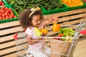 smiling african american kid putting bell peppers in paper bag while sitting in shopping trolley in supermarket
