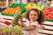 s úsměvem africké americké dítě sedí v nákupní vozík s ananasem v obchodu s potravinami