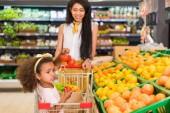 Fotografia afroamericano piccolo bambino seduto nel carrello mentre sua madre portandola vicino reparto frutta in supermercato