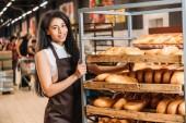 Fotografie mladí africké americké ženské prodavače v zástěře uspořádání čerstvé pečivo v supermarketu