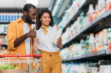 smiling african american man doing thumb up gesture to girlfriend holding milk in supermarket