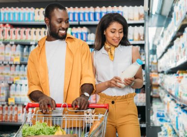smiling african american couple with shopping trolley choosing milk in supermarket