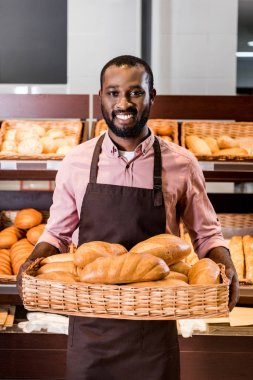 smiling african american male shop assistant in apron holding with loaves of bread in supermarket