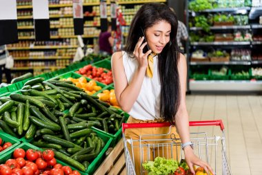 young african american woman talking on smartphone near shopping trolley in grocery store