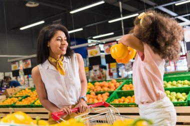 african american woman looking at daughter with bell peppers in supermarket