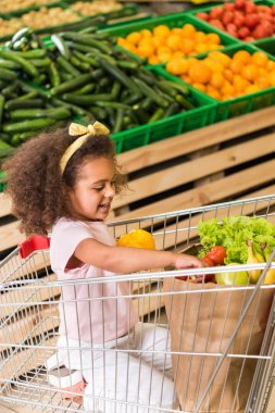 happy african american child sitting in shopping trolley in grocery store