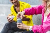 Fotografie oříznutý obraz ženy otevření sody nápoj, zatímco její přítel drží hamburgery na městské ulici