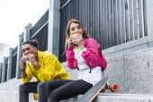 Fotografie selective focus of multicultural couple eating burgers near skateboard at city street