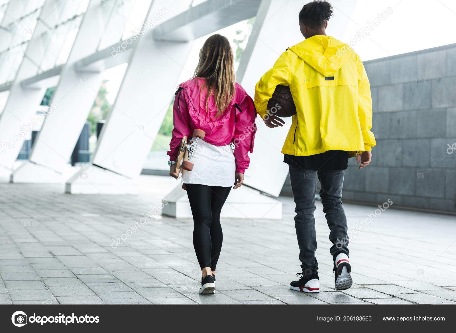 Rear View Couple Walking Skateboard Basketball Ball City Street