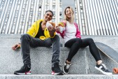 Fotografie low angle view of smiling multiethnic couple of skateboarders showing burgers at city street