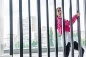 atraktivní stylová žena stojící poblíž kovový plot a koukal na městské ulici