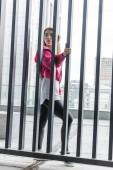 mladé stylové asijských žena stojící poblíž kovový plot a koukal na městské ulici