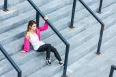 vysoký úhel pohled stylové Asijské žena sedí na schodech v městské ulici