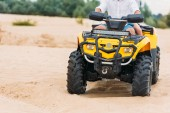 Fotografie cropped shot of couple riding all-terrain vehicle on sand