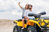 Fotografie attractive young couple taking selfie while sitting on ATV in desert