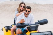 happy young couple taking selfie while sitting on ATV in desert