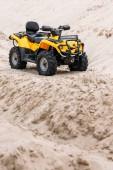 Fotografia moderno giallo veicolo all - terrain in piedi nel deserto