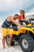 handsome young man pushing atv with his girlfriend got stuck in desert