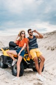 stylish young couple leaning back on ATV in desert