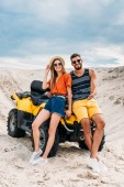 beautiful young couple leaning back on ATV in desert